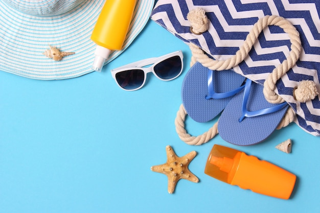 Travel accessories and tropical leaves on a colored background top view