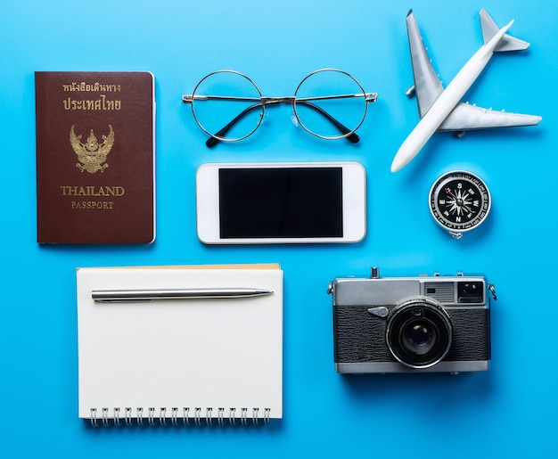 Travel accessories with blank mobile screen on blue background