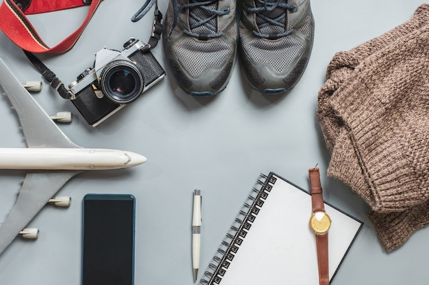 Travel accessories with vintage camera, airplane, shoes, notebook, coat, on ba