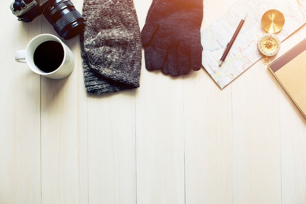 Travel accessories on wooden table with morning light