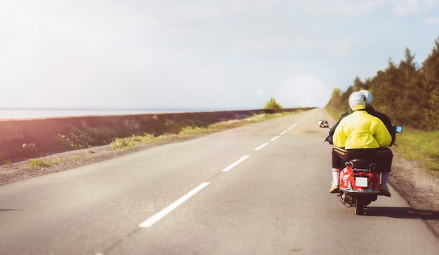 Travel and active lifestyle concept. couple rides a vintage red motor scooter along the coast