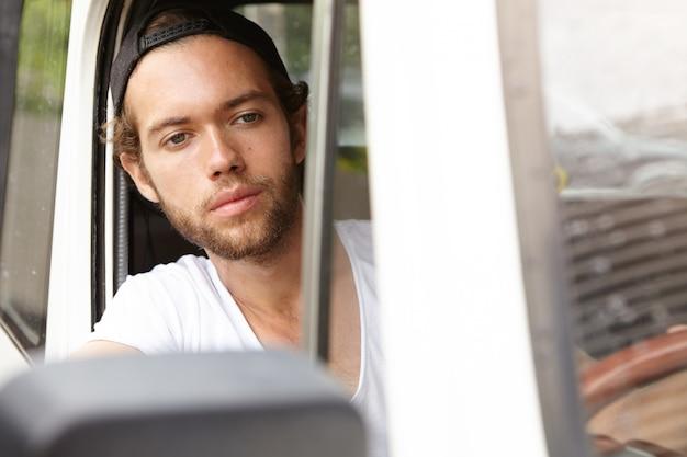 旅行、冒険、アクティブなライフスタイルのコンセプト。彼の白い車の中に座ってスナップバックでスタイリッシュな若い男
