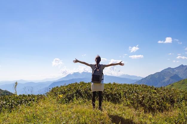 산에서 하이킹으로 여행, 모험 및 트레킹. 한 소녀가 산 꼭대기에 손을 들고 서 있습니다.