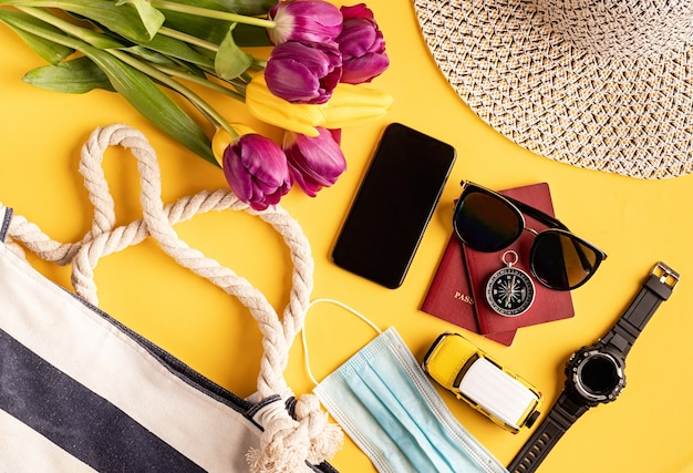 Travel and adventure. flat lay travelling gear with passports, smartphone, sunglasses and compass on yellow background