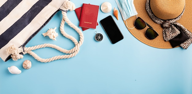 Travel and adventure.flat lay travelling objects with summer hat, smartphone, passport, sunglasses and compass on blue background with copy space