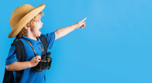 Travel adventure happy kid boy with binoculars pointing finger at space for text traveling child
