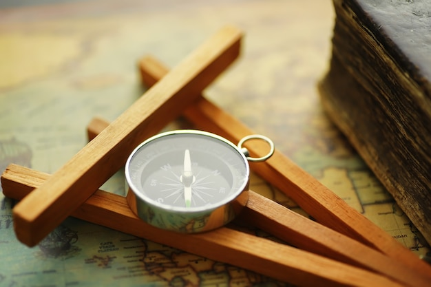 Travel and adventure search concept. vintage aged map with a shabby book and compass. shabby book and compass on the table.