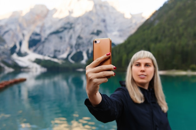 Travel and adventure. travel hiker makes selfie photo on smartphone on beautiful landscape