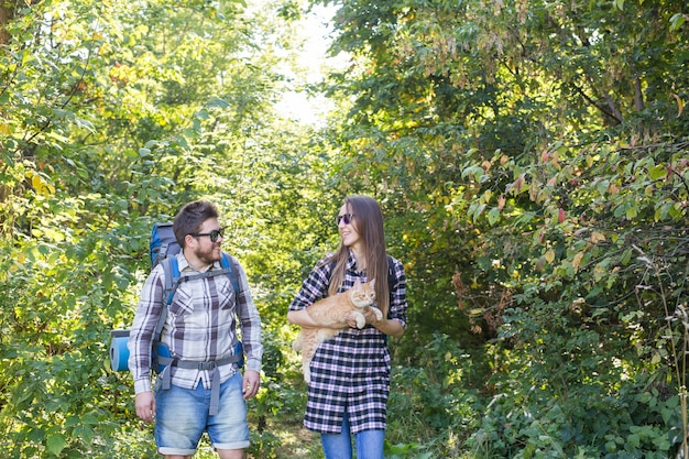 Travel, adventures, hike, tourism and nature concept - tourist couple with cat walking in the woods