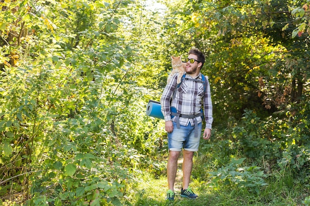 Travel, adventures, hike, tourism and nature concept - tourist with cat walking in the woods