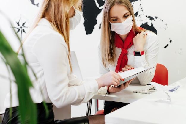 Турагент с клиентом в светлом современном офисе турфирмы, выдает паспорт после регистрации или бронирования рейса. ассистент хранит билеты на самолет в туристическом агентстве для клиентов.