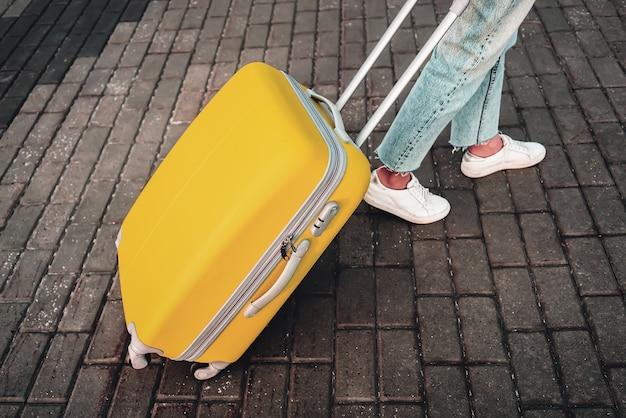 トラベル。空港。黄色のスーツケースを持つ女性。