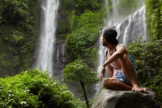 Путешествие и приключения. модный молодой человек в snapback и рюкзаке сидит на камне и смотрит на водопад в красивом зеленом тропическом лесу. босоногий турист отдыхает на скале в джунглях