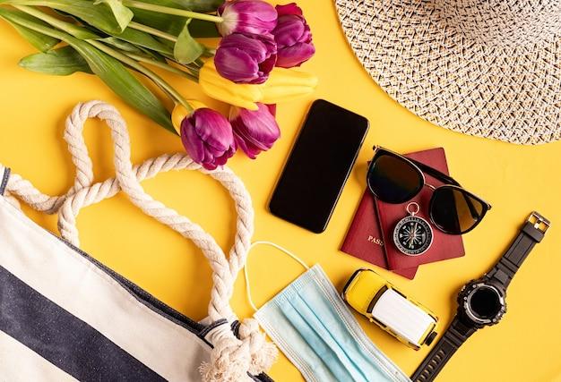 여행과 모험. 노란색 배경에 여권, 스마트 폰, 선글라스와 나침반이있는 평면 평신도 여행 장비