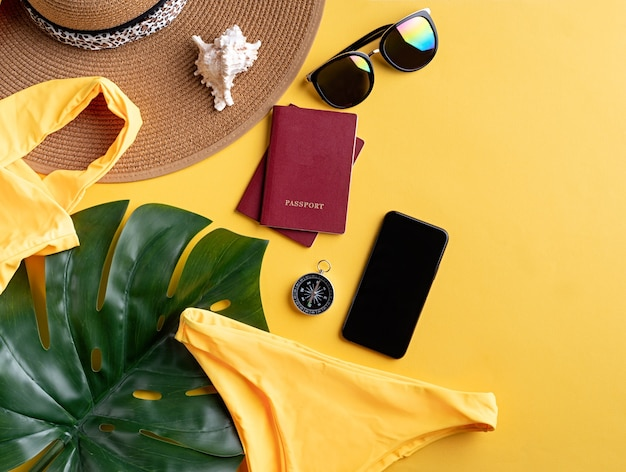 여행과 모험. 수영복, 여권, 스마트 폰, 선글라스 및 복사 공간이있는 노란색 배경에 나침반이있는 평면 평신도 여행 장비