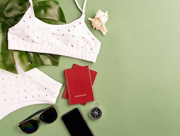 여행과 모험. 몬스 테라 잎, 수영복, 여권, 선글라스와 복사 공간이 녹색 배경에 나침반 플랫 누워 여행 개체