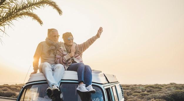 バンの屋根の上に座っている関係のカップルのための愛の旅行とライフスタイルを楽しんでください