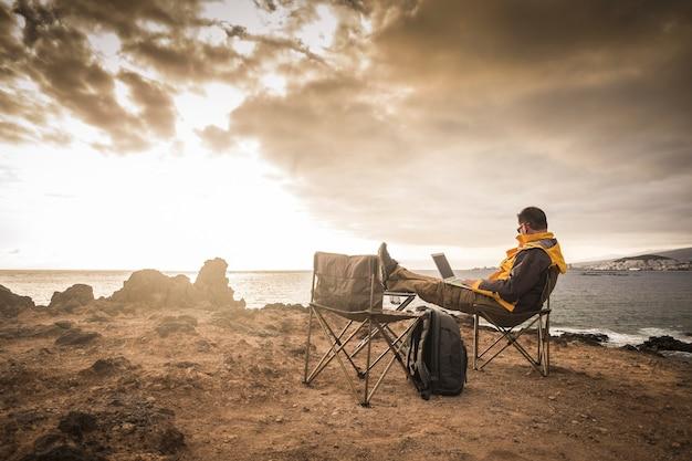 海に沈む素晴らしい夕日の前に座っているノートパソコンのインターネット接続コンピューターで働く孤独な男と一緒に旅行し、アウトドアの人々のコンセプトを楽しむ