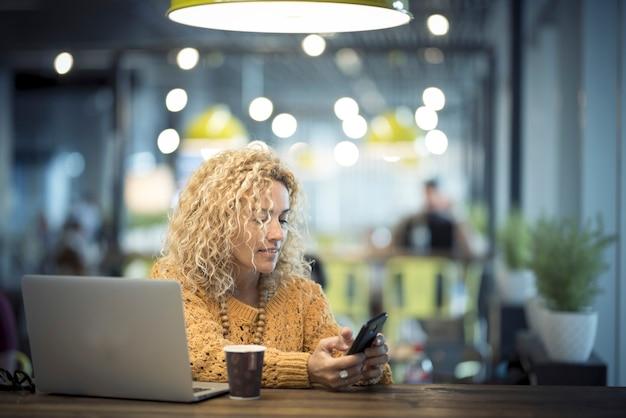 テクノロジーとコーヒーを使った素敵な大人の白人女性との旅行とエブリウィー オフィスのコンセプト