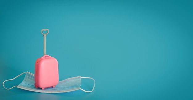 Путешествия и перелеты во время covid-19. мини-чемодан и медицинская маска на синем фоне. свободное место, копировальное пространство. отпуск, каникулы во времена короны. красочный дизайн.
