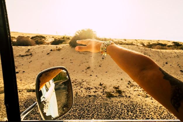 オルタナティブライフスタイルの人々のための旅行と自由の概念-旅行中に風で遊んでいるヴィンテージカーの窓の外の白人女性の手のクローズアップ-砂漠
