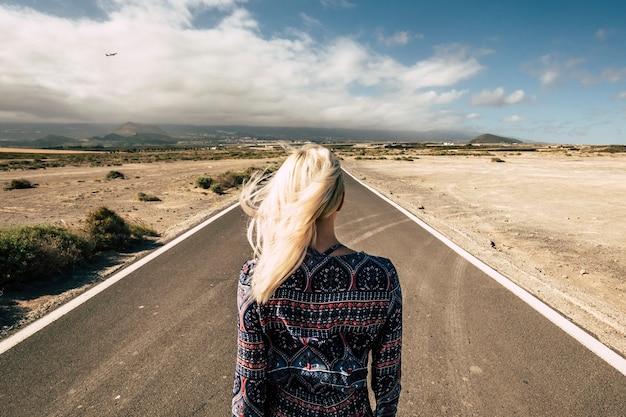 まっすぐな長い道を後ろから見た、金髪の若いミレニアル世代の女の子との旅行と未来の選択のコンセプト