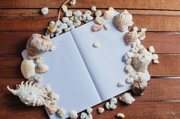 旅行やレジャー、木製のテーブルの上に散らばった貝殻の横にあるノート