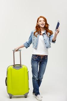 旅行とライフスタイルの概念:若い女性は、夏の旅行のための準備ができているスーツケースと白