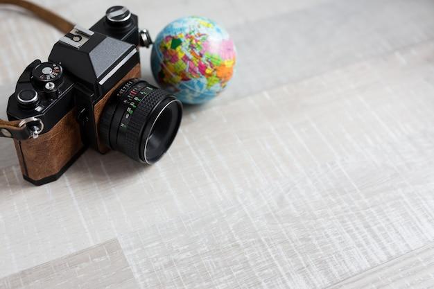 Винтажная камера путешествия и фотографии и маленький глобус на деревянном фоне с копией пространства