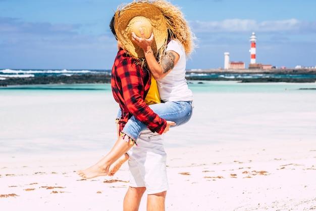麦わら帽子に隠された旅行と夏の人々の休日の休暇のカップルが背景に青い海とビーチで一緒にキスしてロマンチックな愛の関係を楽しんでいます-幸せな生活の新婚旅行 Premium写真