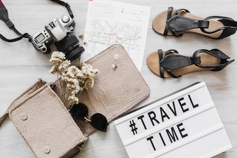 Travel and time text with female accessories on the wooden desk