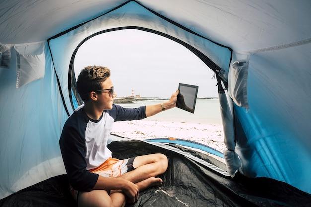 Путешествуйте и используйте технологии для общения для молодого красивого подростка, который сидит в палатке, разбитой лагерем на пляже, и использует планшетный интернет, подключенный к интернету, для отправки сообщений и видеоконференций.