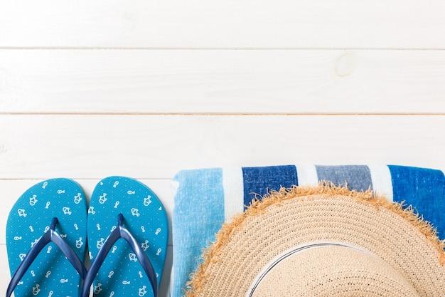 白い木製の背景に旅行や休暇のアクセサリー。コピースペースと上面図の夏休みのコンセプト。