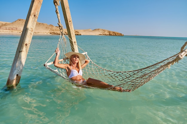 바다에서 해먹에 편안한 여행 및 휴가 개념 여자