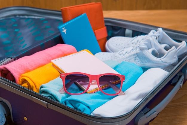 Концепция путешествий и каникул. откройте сумку путешественника с одеждой, аксессуарами, кредитной картой, билетами и паспортом.