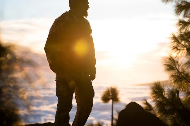 旅行と荒野の自然のライフスタイル山と雲の地平線を背景に自由と素晴らしい夕日を楽しむ一人の立っている男-アウトドアレジャー野生の活動日光フレア