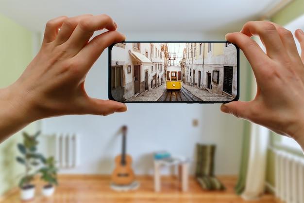 Путешествуйте дома. онлайн-путешествие в лиссабон, португалия через смартфон. легендарный желтый трамвай на экране