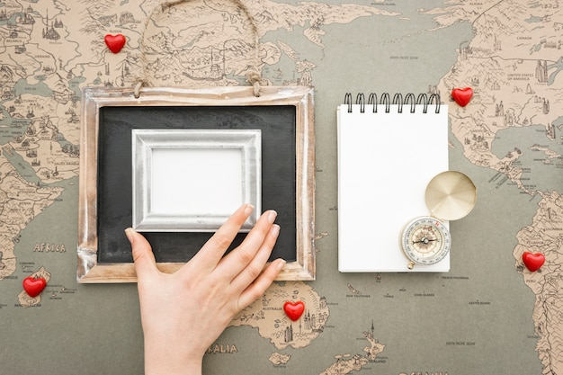 Travel background with hand placing a frame