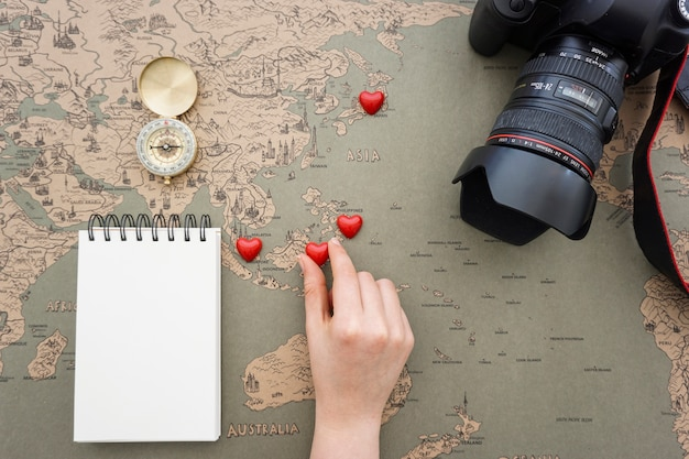 Travel background with hand placing hearts on a world map