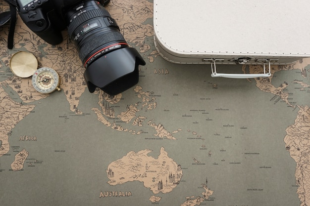 Travel background with suitcase, camera and compass