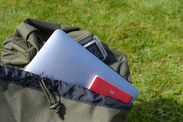 Travel backpack with passport, laptop and camera. camping trip concept.