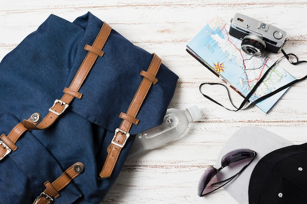 Travel bag and accessories on wooden background