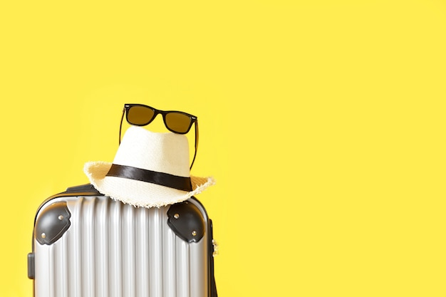 コピースペース付きの黄色の背景にトラベルバッグ、荷物、麦わら帽子、サングラス。スーツケース、帽子、黄色の背景に分離された黒いサングラス。夏の旅行のコンセプト。