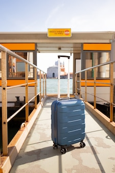 Travel bag near river bus at sunny day in venice, italy.