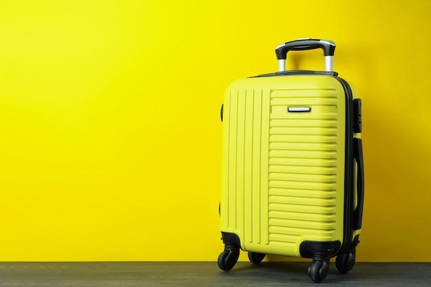 노란색 바탕에 여행 가방