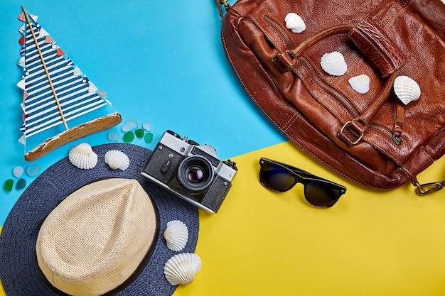 Дорожная сумка, солнцезащитные очки, парусник ручной работы и фотоаппарат на желто-синем фоне