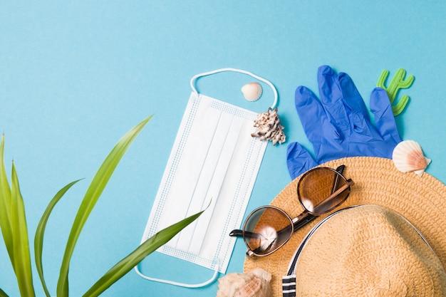 Концепция запрета на поездки, шляпа, солнцезащитные очки, ракушки, маска и резиновые перчатки