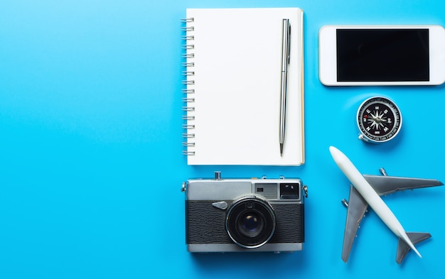 Travel blogger accessories with copy space on blue background