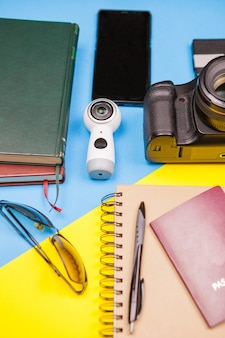 Комплект travel blogger из зеркалки и экшн-камеры рядом с книгами, бумажным блокнотом, солнцезащитными очками, смартфоном и паспортом.