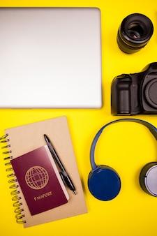 Комплект блоггера путешествия на желтом фоне. плоский вид сверху